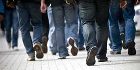 Menschen laufen nach Schichtende aus einem Werk